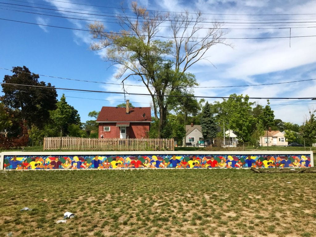 photo of art mural above lawn with trees and houses in background