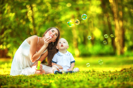 Mother and baby blowing bubbles in the park.