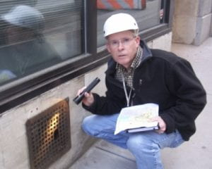 photo of Bobby Corrigan wearing a hard hat, holding a clipboard in one hand and a flashlight in the other pointing out a rusted wall grid plate with a hole large enough for a rat to fit through.