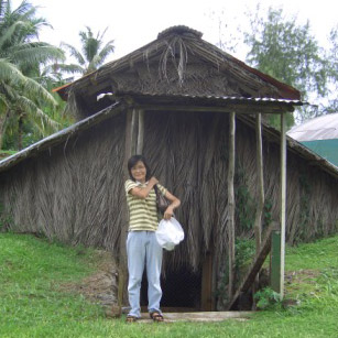 Mana's mother outside the mushroom hut in Samoa
