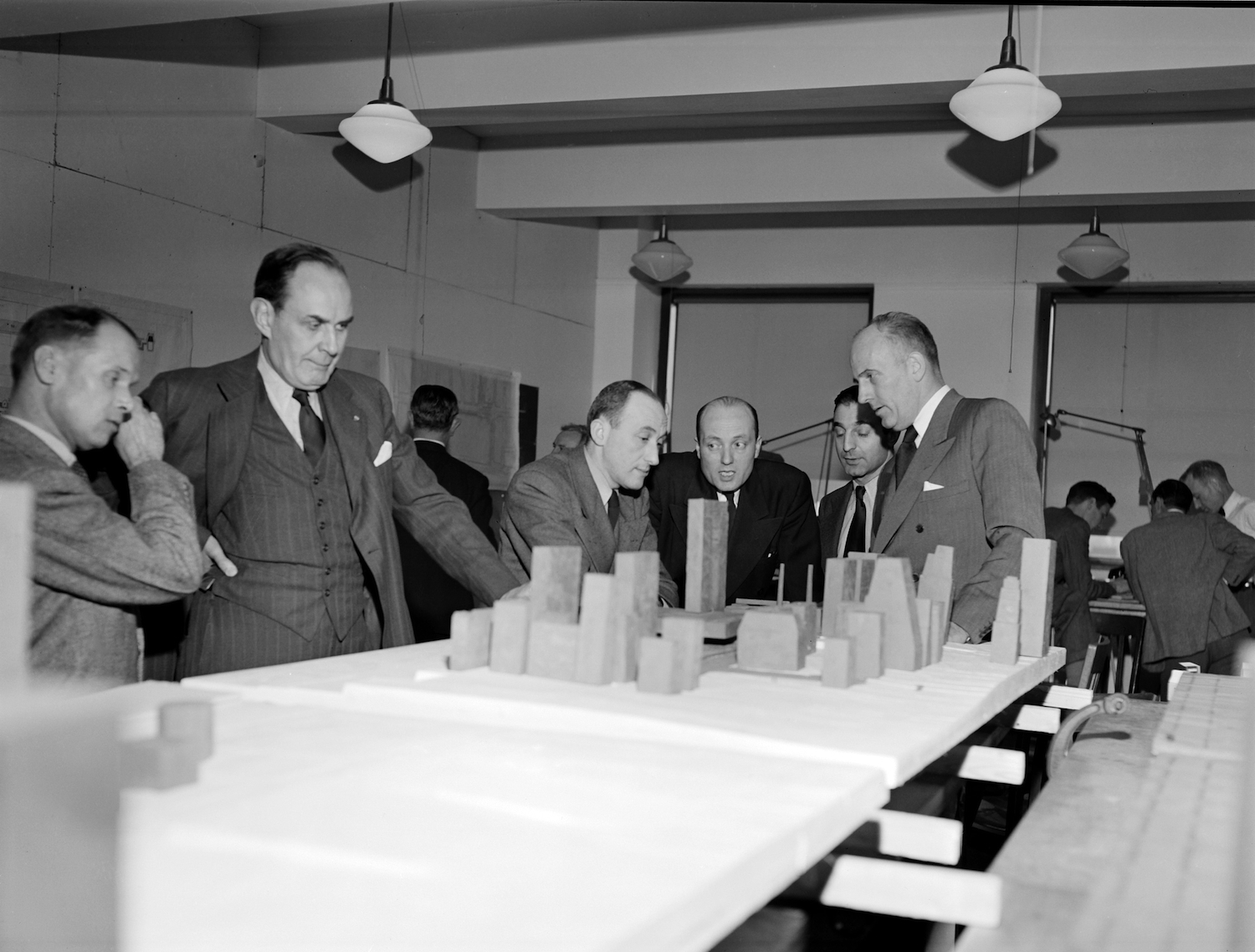 GIL CLARKE (SECOND FROM LEFT) STUDYING MASSING PLAN (HARRISON AND ABRAMOVITZ AT END OF TABLE) - UNITED NATIONS ARCHIVES