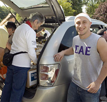 Volunteers unload the car of Curtis Roddy, whose fraternity contributed nearly 1,200 cans of food during the Stephen E. Garner Day of Caring.