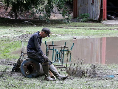man sitting outside of flooded barn