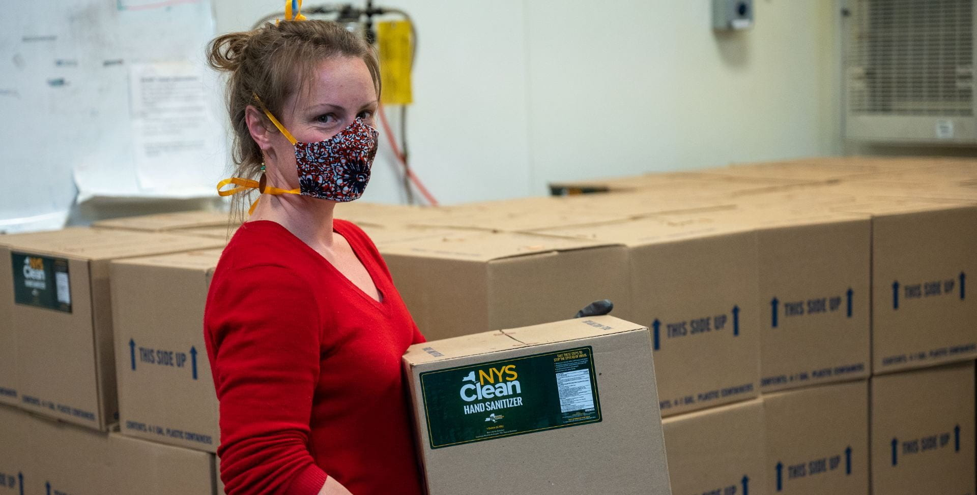 Woman in face covering holding box of NYS Clean Hand Sanitizer