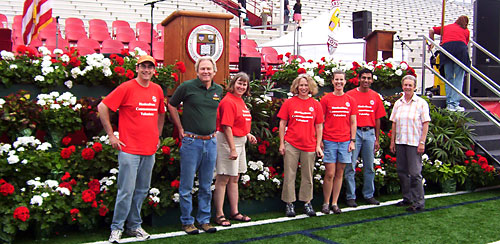 Graduation volunteers from the Department of Horticulture pose with their work at Schoellkopf Field stage.