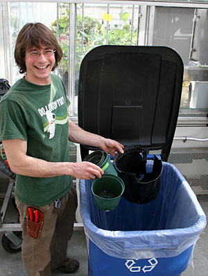 Greenhouse grower Jacob Wszolek recycles pots at the Plant Science Greenhouses.