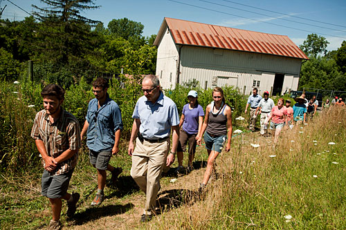 President Skorton heads to the field with student managers at Dilmun Hill Student Farm