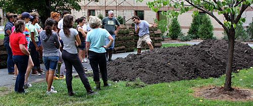Turf specialist Frank Rossi explains to students how to shape the pile of compost prior to laying sod.