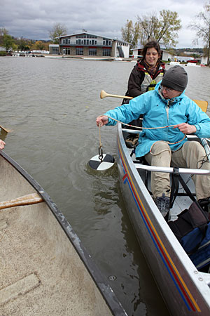 Students use a Secchi disk to measure light penetration in Cayuga Inlet near Cornell's Robison Boathouse
