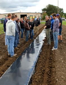 Students inspect newly laid plastic mulch.