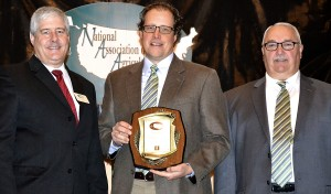 Travis Park (center) accepts the Outstanding Cooperation Award from Ken Couture, 2011-2012 NAAE President, and Mike Williams, Association Sales Director for Forrest T. Jones, the sponsor of the Outstanding Cooperation Award, November 30 at the NAAE annual convention in Atlanta.