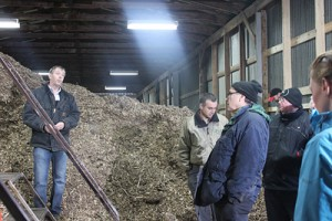 Larry Smart answers questions from attendees inside the willow chip drying barn. It takes about 70 to 100 tons of willow for the boiler to produce enough heat for the winter season. Sarah Thompson photo.
