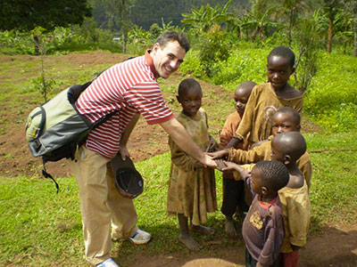 Graduate student Bryan Sobel with children from the Rwandan village where he worked with women to teach mushroom farming skills.