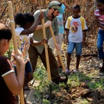 Bryan Sobel, MS candidate in the Graduate Field of Horticulture, demonstrates how to break ground for a garden bed. The students built two gardens outside the school in Barranco, a Garifuna Village in the Toledo District in southern Belize.