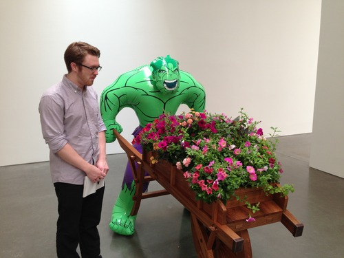 Matt Spencer, an industrial designer working for Jeff Koons, stands beside the sculpture Hulk (Wheelbarrow) at the Gagosian Gallery in New York City, Photo by Chris Wien