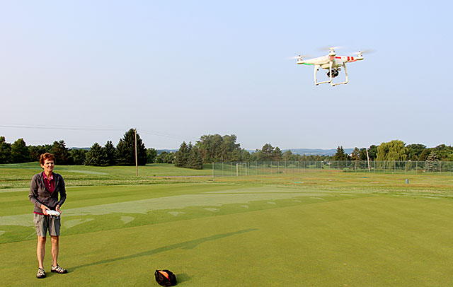 Mary Thurn, research support specialist with the Cornell Turfgrass Program, demonstrates how she uses the [make and model] drone to get an aerial view of turf research plots.