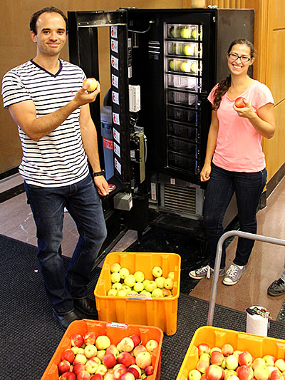 SoHo members Jeremie Blum and Annika Kreye, PhD candidates in the Graduate Field of Horticulture, load the apple machine in its new location in the entrance to Mann Library.