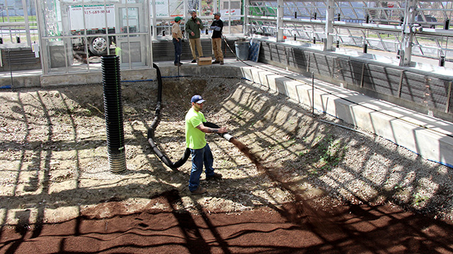 Workers blow growinig medium into the new Liberty Hyde Bailey Conservatory.