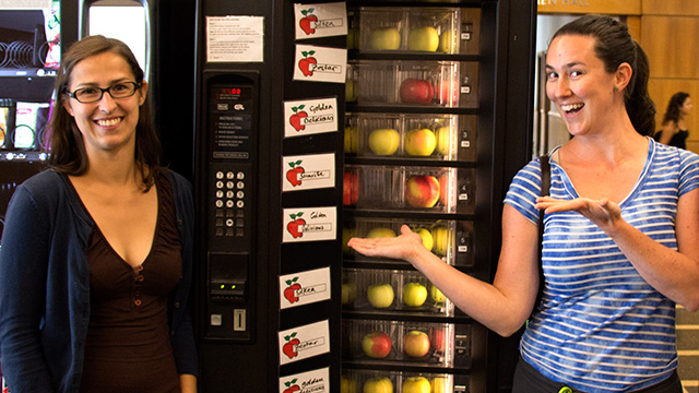 Horticulture graduate students Annika Huber and Juana Muñoz Ucros stocking the apple machine with varieties picked by grad students last weekend at Cornell Orchards.