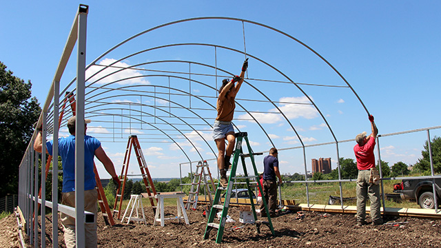 Tilebein, Hutchinson and Thompson Research Farm farm manager Steve McKay install rafters.