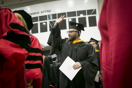 Justin France waves to family and friends after receiving recognition for earning his master's degree in horticulture. (Photo: Jason Koski/University Photography)