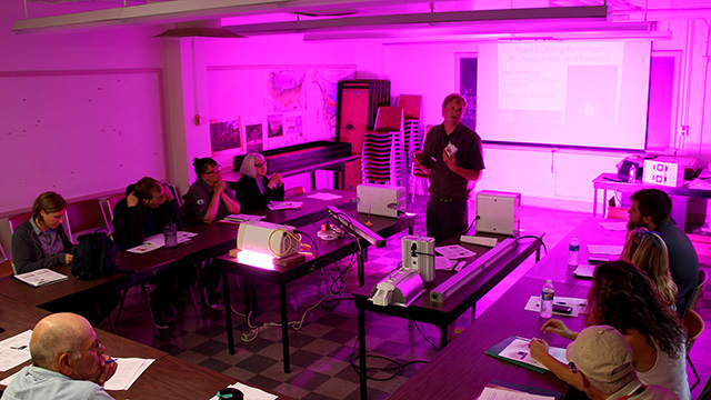 Horticulture associate professor Neil Mattson demonstrates the latest in greenhouse lighting systems at the greenhouse workshop.