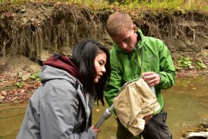 Students Stevanica Augustine, left, and Jonas Soe examine invertebrates along the streams that feed into Lake Trema
