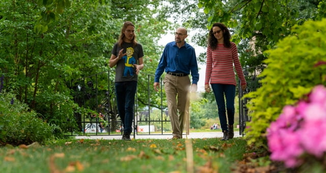 rakow flanked by two students walking through garden