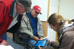 Farmers Robert and Rodney Donald review the Adapt-N tool with Cornell extension associate Bianca Moebius-Clune. They saved thousands of dollars after applying Adapt-N recommendations during a trial at their Moravia farm.