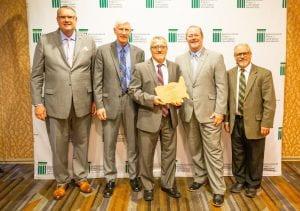 5 men standing with an award