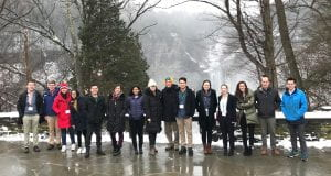 group of students standing in front of a waterfall