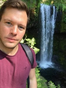 man in front of waterfall