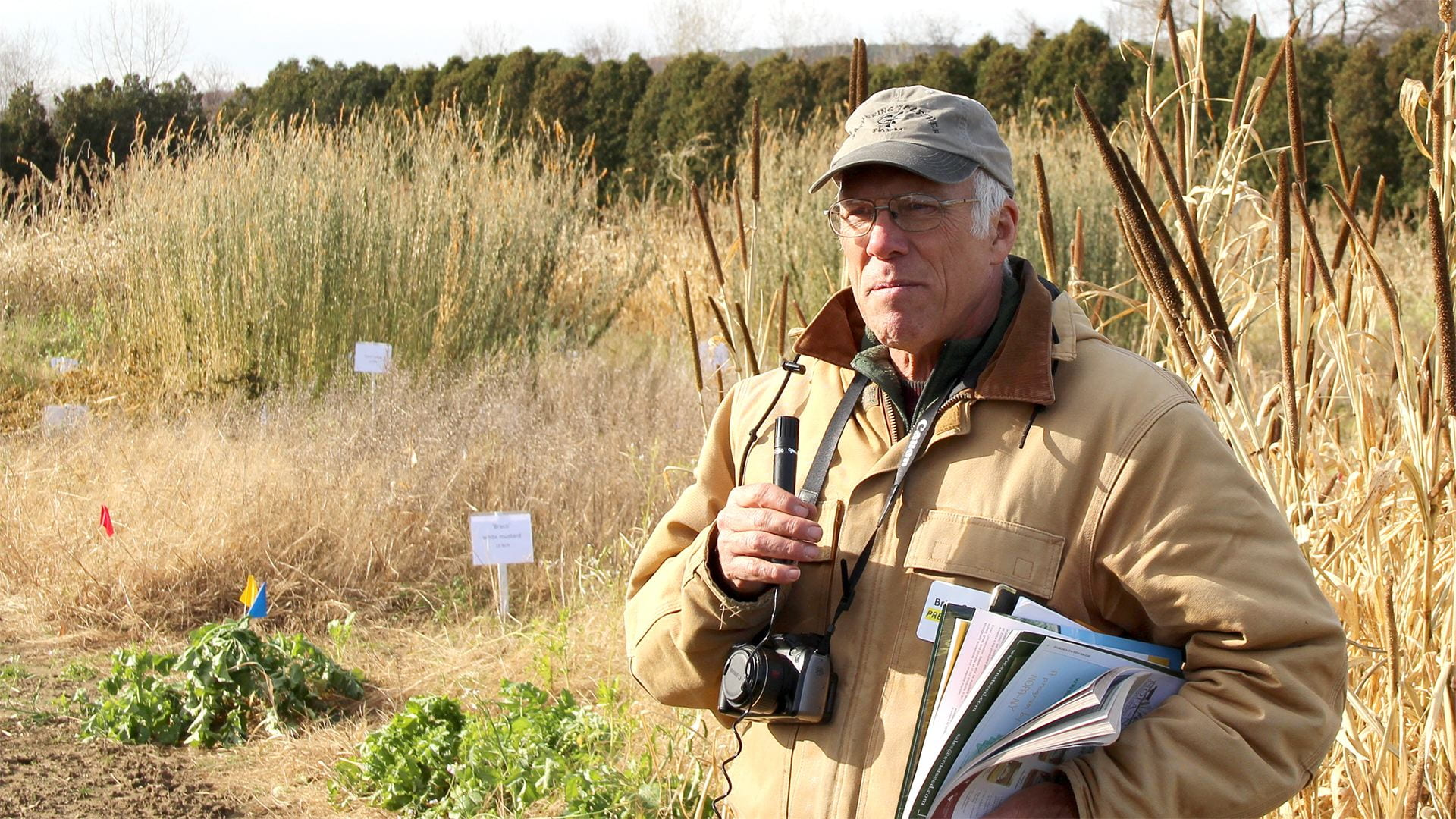 Brian Caldwell with mic, camera and stack of handouts at field day witn cover and forage crop plots in the background