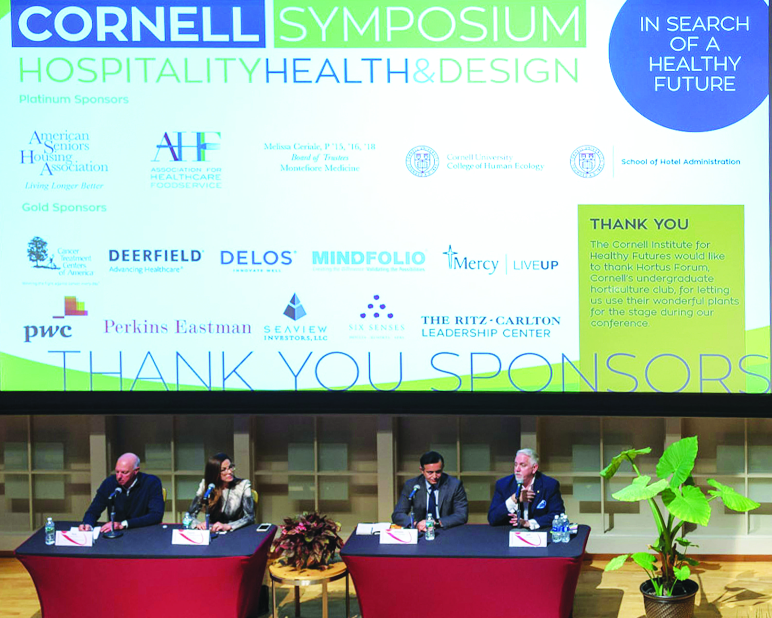 Photo of powerpoint slide containing sponsors for a CIHF conference, displayed during the conference in a lecture hall with people sitting beneath it on a stage