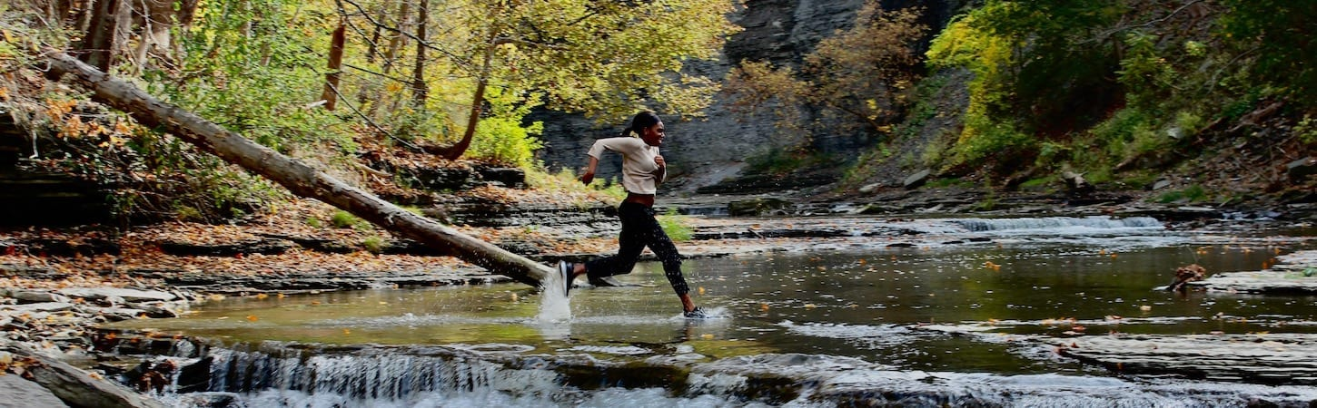 Photo of person running next to waterfall