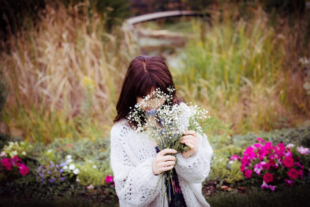 Photo of a girl hiding behind flowers, by Julia Therese McFadden, submitted for the CIHF photo competition