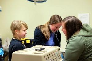CU vet student volunteering at Schuyler Wellness Clinic discusses procedures with your pet owner