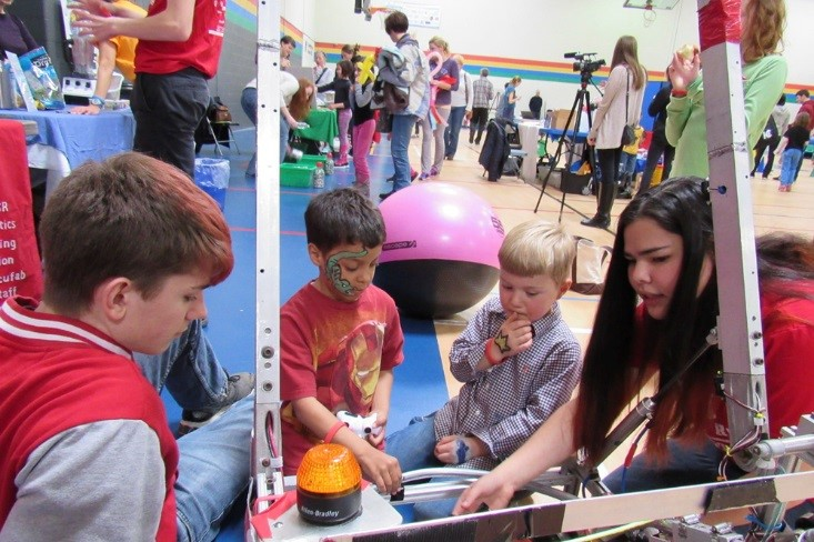 Senior Kieran Loehr and junior Abigail Lee talk about the 2014 robot (now used as a demo robot) at the YMCA Healthy Kids Day. At the demo events team members show kids how the robot moves and plays games, and encourage them to come up to touch the robot and ask questions.