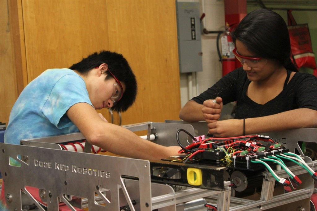 Seniors Pooja Reddy and Kenzo Uchigasaki work together on the 2016 robot frame, even as electronic components are being installed at the front. The team's electronics subteam designs and assembles all of the robot's electronics. Other subteams handle programming, media, CAD, and machining.