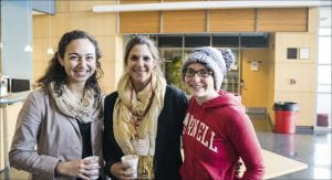 Three students at the latest Coffee and Conversation event smile at the camera