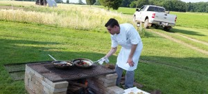 Chef Sam Strock prepares menu items over open fire at Rettland Farm.