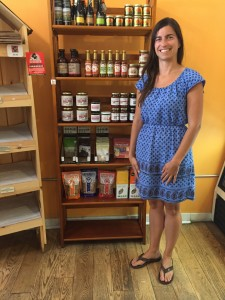 Nana Monaco stands in front of a shelf containing goods from the Finger Lakes area. Photo by Carli Fraccarolli