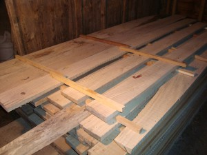 Lumber should be stickered immediately after sawing, ideally as the boards come off the mill.  In door storage, as illustrated, is ideal if space is available.