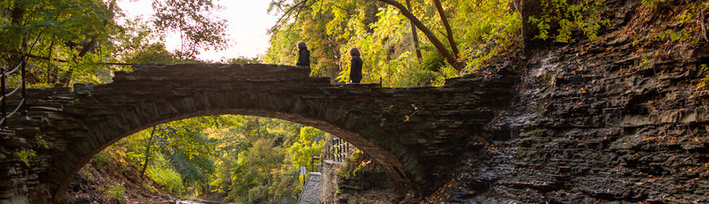 Students on Cascadilla Creek Bridge in fall. The iconic bridge in Cascadilla Gorge. ©️Cornell University Marketing Group