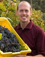 Matthew Clark headshot, holding a bin of grapes