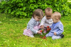 Three cute girls playing with fruit in the garden