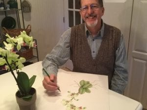 Doug pretends to work on a botanical drawing or the orchid sitting on the table in front of him