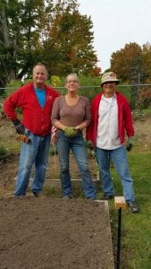 Three Master Gardener Volunteers standin in a garden