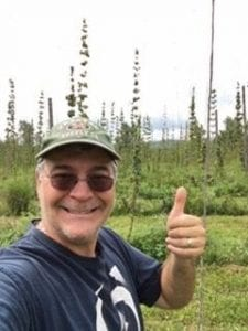 Joe giving a thumbs up standing in front of a hop yard