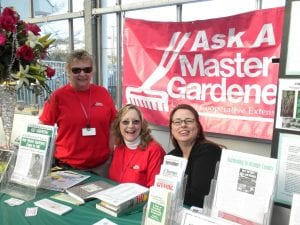 "Three Master Gardener Volunteers staff an ""Ask a Master Gardener Table"""